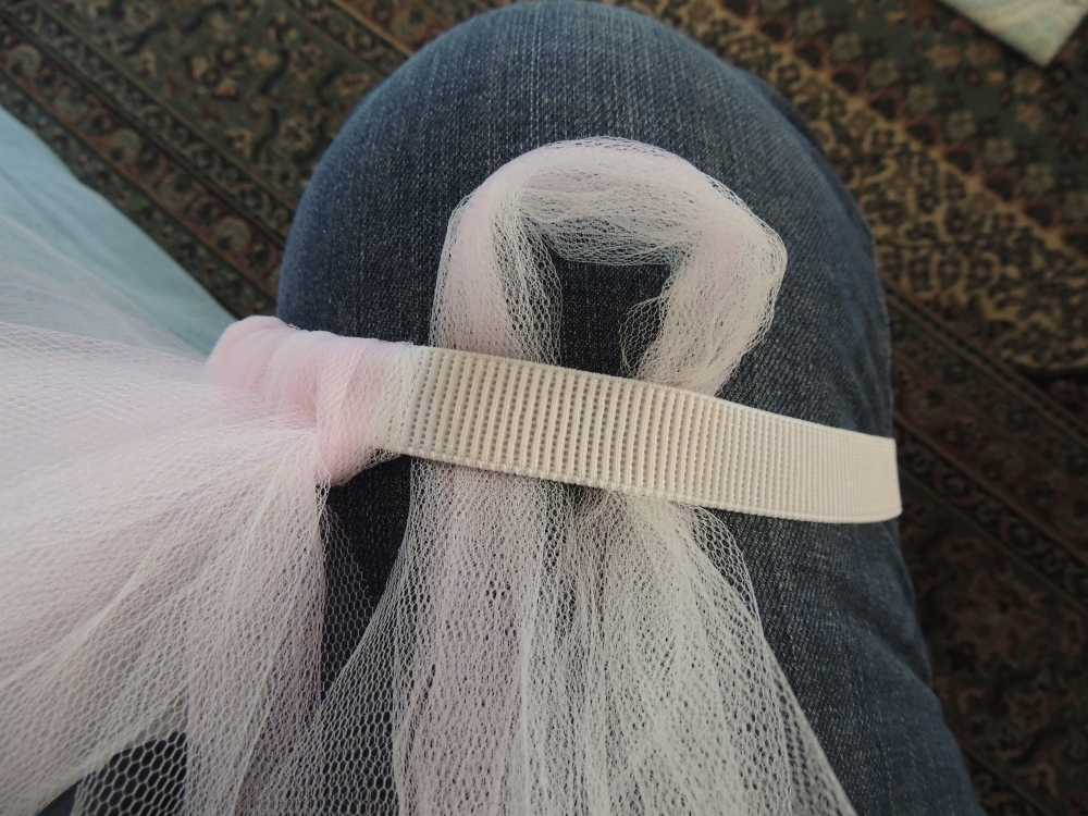 Using three tulle strips, form a loop in the middle and place under the elastic