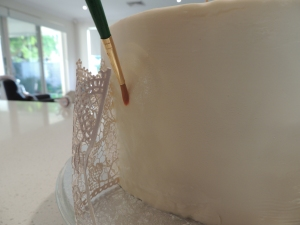 Apply water with a paintbrush and carefully add the cake lace